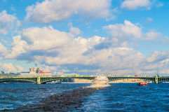 Trinity Bridge and touristic pleasure boat floating under the bridge span at Neva River in St Petersburg, Russia Royalty Free Stock Images
