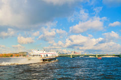 Trinity Bridge and touristic pleasure boat floating on water area of Neva River in St Petersburg, Russia. ST PETERSBURG,RUSSIA-OCTOBER 3, 2016. Trinity Bridge Royalty Free Stock Photography