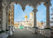 Trinity Cathedral in the Sergius Lavra. In Sergiev Posad on a winter sunny frosty day through the arches of the refectory  building Stock Photo