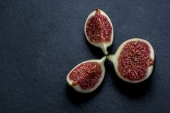Trinity of chopped fresh figs on black shale Stock Photography