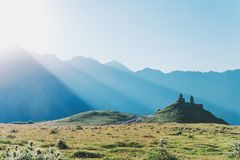 Trinity Church in mountains on the background of sunset rays in. The Caucasian mountains Stepantsminda beautiful mountain landscape Royalty Free Stock Photo