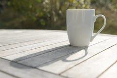 Trinkbecher auf einem Holztisch im Sun Stockbilder