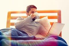 Trinken im Kaffee im Bett mit Laptop Stockfotografie