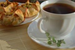 Trinken Sie schwarzen Tee mit Minze und Torten mit Kartoffeln und Fleisch für das Frühstücksmittagessen Lizenzfreie Stockfotos