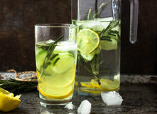 Trinken Sie Wasser von der Gurke und vom Kalk mit Rosmarin in einem Glasgefäß und in einem Glas Stockbild