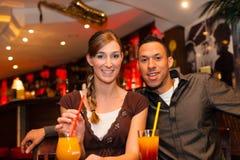 Trinkende Cocktails der jungen Paare im Stab Lizenzfreie Stockfotos