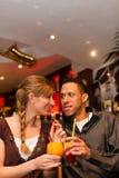 Trinkende Cocktails der jungen Paare im Stab Stockbild
