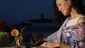 Trinkende Erfrischung der schönen Dichterin im Strandcafé, Roman in Notizbuch schreibend stock footage