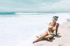 Trinkende Kokosnuss der Frau auf dem tropischen Strand lizenzfreie stockbilder