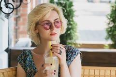 Trinkende Limonade der jungen europäischen Frau in einem Café Stockbild