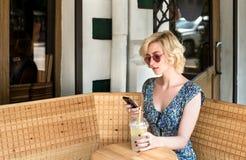 Trinkende Limonade der jungen europäischen Frau in einem Café Lizenzfreies Stockfoto