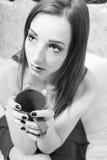 Trinkende schöne junge Frau des Tees, die auf Bett im Kleid hält Schale und oben schaut sitzt Porträtnahaufnahme Lizenzfreies Stockbild