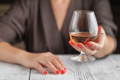 Trinkender Alkohol der Frau auf dunklem Hintergrund Fokus auf Weinglas Stockfoto