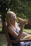 Trinkender Alkohol der Frau von einer Glasflasche in der Papiertüte Stockfotografie