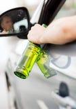 Trinkender Alkohol des Mannes beim Fahren des Autos Stockfotos