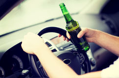 Trinkender Alkohol des Mannes beim Fahren des Autos Stockbild