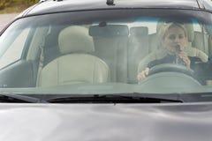 Trinkender Alkohol des weiblichen Fahrers im Auto Lizenzfreie Stockfotos