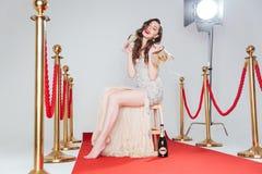 Trinkender Champagner der Frau auf rotem Teppich Stockfotos