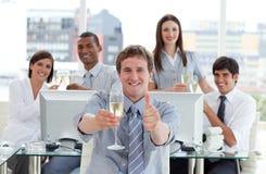 Trinkender Champagner des konkurrierenden Geschäftsteams lizenzfreie stockbilder