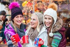 Trinkender Eierpunsch der Frau auf deutschem Weihnachtsmarkt Lizenzfreie Stockbilder