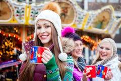 Trinkender Eierpunsch der Frau auf deutschem Weihnachtsmarkt Stockfotos