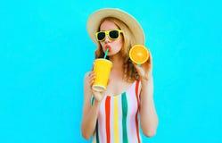 Trinkender Fruchtsaft der Sommerportr?tfrau, der in ihrer Handscheibe der Orange im Strohhut auf buntem Blau h?lt stockfoto