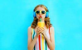 Trinkender Fruchtsaft der stilvollen Frau des Porträts, der Musik in den drahtlosen Kopfhörern auf buntem Blau hört lizenzfreie stockfotografie
