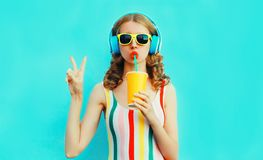 Trinkender Fruchtsaft des kühlen Mädchens des Porträts, der Musik in den drahtlosen Kopfhörern auf buntem Blau hört stockbilder