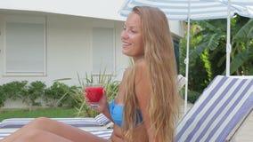 Trinkender Fruchtsaft des schönen Mädchens beim Sitzen durch das Pool stock footage