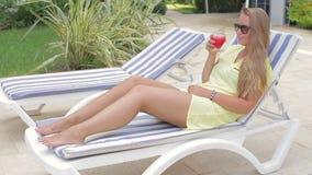 Trinkender Fruchtsaft des schönen Mädchens beim Sitzen durch das Pool stock video