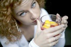Trinkender Fruchttee des Mädchens Lizenzfreie Stockbilder