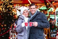 Trinkender gewürzter Wein der Paare auf Weihnachtsmarkt Stockbild