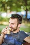 Trinkender Instantkaffee des jungen Mannes in einem Park stockbild