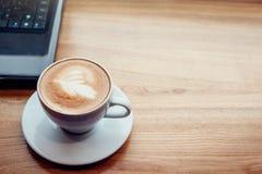 Trinkender Kaffee bei der Anwendung eines Laptops im Café Tasse Kaffee mit Laptop im Guss des Fensters Stockfotografie