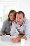 Trinkender Kaffee der älteren Paare und mit Tablette Lizenzfreies Stockfoto