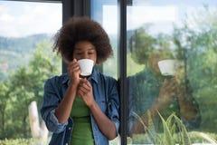 Trinkender Kaffee der Afroamerikanerfrau, der heraus das Fenster schaut Stockfoto