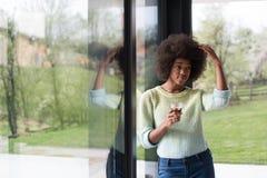 Trinkender Kaffee der Afroamerikanerfrau, der heraus das Fenster schaut Stockfotografie