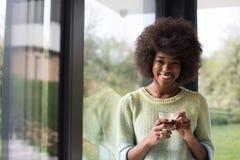 Trinkender Kaffee der Afroamerikanerfrau, der heraus das Fenster schaut Stockfotos