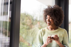 Trinkender Kaffee der Afroamerikanerfrau, der heraus das Fenster schaut Stockbilder