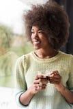 Trinkender Kaffee der Afroamerikanerfrau, der heraus das Fenster schaut Lizenzfreie Stockbilder
