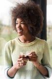Trinkender Kaffee der Afroamerikanerfrau, der heraus das Fenster schaut Lizenzfreie Stockfotografie
