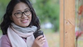 Trinkender Kaffee der Asiatin draußen stock video footage