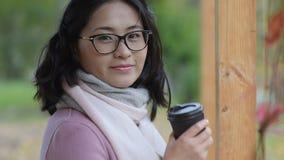 Trinkender Kaffee der Asiatin draußen stock video