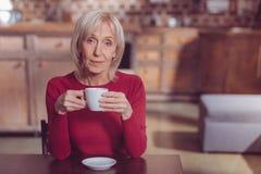 Trinkender Kaffee der begeisterten reifen Frau stockfotografie