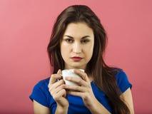 Trinkender Kaffee der ernsten Frau über rosa Hintergrund Stockfoto