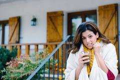 Trinkender Kaffee der Frau außerhalb des Hauses auf dem Einfrieren des kalten Herbstes lizenzfreies stockbild