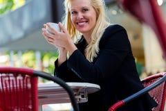 Trinkender Kaffee der Frau draußen im Stadtcafé Stockbild