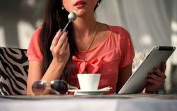 Trinkender Kaffee der Frau und Lesen des Ebuches Lizenzfreie Stockbilder