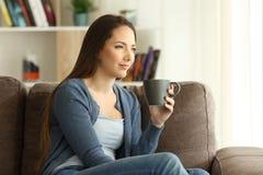 Trinkender Kaffee der Frau und Schauen weg auf einer Couch stockbild