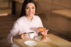 Trinkender Kaffee der Geschäftsfrau mit Hörnchen stockfoto